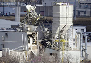 Photo - The International Nutrition plant is shown with wreckage in Omaha, Neb., where a fire and explosion took place Monday, Jan. 20, 2014. At least nine people have been hospitalized and others could be trapped at the animal feed processing plant. (AP Photo/Nati Harnik)