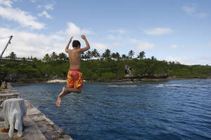 Photo - In this Wednesday, June 4, 2014 photo, a boy jumps from a wharf in Alofi, Niue. Severe population decline on the tiny Pacific atoll is threatening a culture that dates back more than 1,000 years. (AP Photo/Nick Perry)