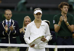 Photo - Eugenie Bouchard of Canada holds the runners up trophy after being defeated by Petra Kvitova of Czech Republic in the women's singles final match at the All England Lawn Tennis Championships in Wimbledon, London, Saturday, July 5, 2014. (AP Photo/Sang Tan)