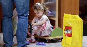 Photo - Alexis Osgood, 2, sits outside a shoe store with her Lego bag next to her to try on a pair of sneakers as her mother, Caitlin, looks on at the South Shore Mall in Braintree, Mass. AP Photo