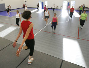 Photo - In this archive photo, instructor Ruth Ann Dreyer leads a fitness routine during a Body & Soul fitness class at Holy Trinity Lutheran Church in Edmond. <strong>PAUL HELLSTERN - The Oklahoman</strong>