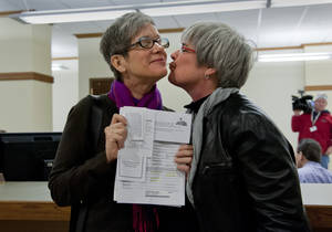 Photo - Laurie Johnson and Margaret Witt celebrate attaining their marriage license on Thursday, Dec. 6, 2012, at the Spokane County Courthouse in Spokane, Wash.  Washington state now joins several other states that allow gay and lesbian couples to wed. Gov. Chris Gregoire signed a voter-approved law legalizing gay marriage. Because the state has a three-day waiting period, the earliest that weddings can take place is Sunday. (AP Photo/The Spokesman-Review, Dan Pelle)  COEUR D'ALENE PRESS OUT