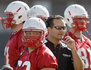 Photo -   FILE - In this March 10, 2012 file photo, Nebraska offensive coordinator Tim Beck works with players, including Ben Cotton, right and Ryan Klachko, center left, on the opening day of NCAA college football spring practice in Lincoln, Neb. No. 17 Nebraska believes its offense is about to make a big jump in Tim Beck's second year as coordinator. Last year, when the Cornhuskers were 66th in offense, Beck was just learning how to be a coordinator, and his players were just learning his system. (AP Photo/Nati Harnik, File)