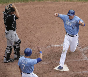 Photo - Kansas City Royals' Elliot Johnson (23) and David Lough (7) celebrate after scoring on a fielding error hit into by Alcides Escobar during the eighth inning of a baseball game against the Chicago White Sox, Sunday, June 23, 2013, in Kansas City, Mo. (AP Photo/Charlie Riedel)