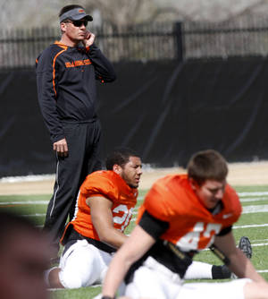 Photo - Oklahoma State football coach Mike Gundy walks through rows of players stretching during practice on Tuesday, April 1, 2014 at the outside fields of the Sherman E. Smith training facility at Oklahoma State University in Stillwater. The Cowboys will be forced to miss one day of practice each week this coming season because of an APR penalty from the NCAA. PHOTO BY KT KING, For The Oklahoman