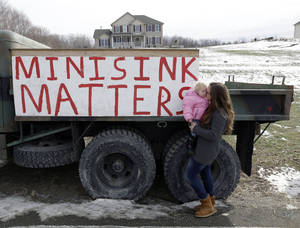 Photo - In this Thursday, Feb. 7, 2013 photo, Leanne Baum holds her daughter Hannah on a road outside their home in Minisink, N.Y. The construction site for a natural gas compressor station is across the road from the house. (AP Photo/Mike Groll)