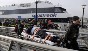 photo - An injured passenger from the Seastreak Wall Street ferry is taken to an ambulance, in New York,  Wednesday, Jan. 9, 2013. The ferry from Atlantic Highlands, N.J., banged into the mooring as it arrived at South Street in lower Manhattan during morning rush hour, injuring as many as 50 people, at least one critically, officials said.(AP Photo/Richard Drew)