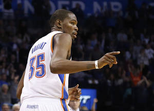 Photo - Oklahoma City Thunder forward Kevin Durant gestures to a teammate after hitting a basket in the fourth quarter of an NBA basketball game against the Memphis Grizzlies in Oklahoma City, Friday, Feb. 28, 2014. Oklahoma City won 113-107. (AP Photo/Sue Ogrocki)