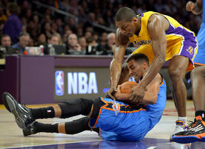 Photo - Oklahoma City Thunder guard Thabo Sefolosha, left, of Switzerland, battles Los Angeles Lakers forward Metta World Peace for the loose ball during the first half of their NBA basketball game, Friday, Jan. 11, 2013, in Los Angeles. (AP Photo/Mark J. Terrill) ORG XMIT: LAS103