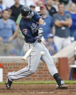 Photo - Atlanta Braves' Christian Bethancourt hits an RBI single against the Chicago Cubs during the ninth inning of a baseball game on Friday, July 11, 2014, in Chicago. The Chicago Cubs won 5-4. (AP Photo/Andrew A. Nelles)