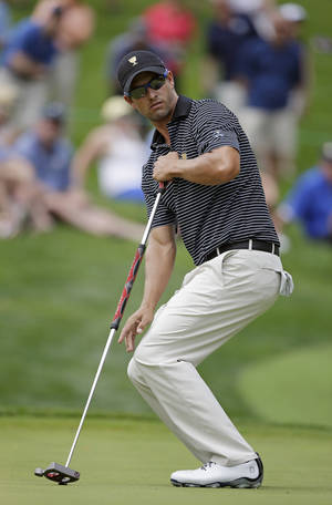 Photo - International team player Adam Scott, of Australia, reacts to a missed putt on the fourth hole during a foursome match at the Presidents Cup golf tournament at Muirfield Village Golf Club, Friday, Oct. 4, 2013, in Dublin, Ohio. (AP Photo/Darron Cummings)
