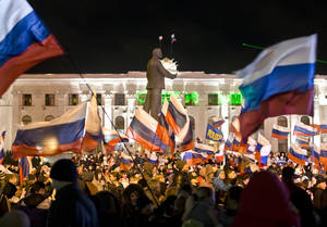 Photo - Pro-Russian people celebrate in Lenin Square, in Simferopol, Ukraine, Sunday, March 16, 2014. Polls have closed in Crimea's contentious referendum on seceding from Ukraine and seeking annexation by Russia. The vote, unrecognized both by the Ukrainian government and the West, was held Sunday as Russian flags fluttered in the breeze and retirees grew weepy at the thought of reuniting with Russia. (AP Photo/Vadim Ghirda)