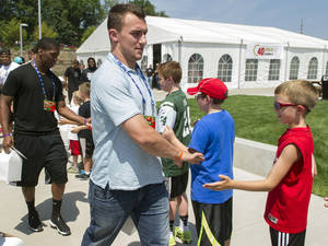 Photo - Cleveland Browns rookie Johnny Manziel greets fans as he leaves the 2014 NFL Rookie Symposium at the Pro Football Hall of Fame in Canton, Ohio, Saturday, June 28, 2014. (AP Photo/Phil Long)