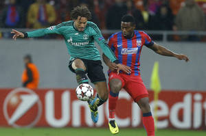 Photo - FILE - In this Nov. 26, 2013, file photo, Schalke's Jermaine Jones, left, controls the ball ahead of Bucharest's Fernando Varela during their Champions League soccer match at the National Arena in Bucharest, Romania. Jones, an American midfielder, has been loaned to the Turkish club Besiktas from Schalke for the rest of the season after telling the Bundesliga team he wanted a move before the winter transfer window closes Friday, Jan. 31, 2014. (AP Photo/Vadim Ghirda, File)