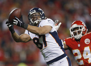 Photo - FILE - In this Dec. 1, 2013 file photo, Denver Broncos wide receiver Eric Decker (87) makes a touchdown reception against Kansas City Chiefs cornerback Brandon Flowers during an NFL football game in Kansas City, Mo. The New York Jets have agreed to terms with Decker, considered by many the top free agent at his position. (AP Photo/Ed Zurga, File)
