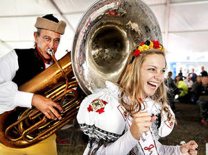 Photo - Tuba player David Masopust startles Abby Rideout during the annual Czech Festival in downtown Yukon. She is a member of the Oklahoma Czech Folk Dancers. PHOTO BY JIM BECKEL  <strong>Jim Beckel - AP</strong>