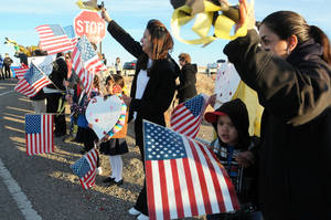 Photo - Supporters of Berrendo Middle School hold welcome backs signs and balloons while waving American flags and yellow ribbons, greet returning students, parents and teachers back to the school, Thursday, Jan. 16, 2014,  in Roswell, N.M. Two days after the shooting that involved three students and forced the evacuation and closing of the school. (AP Photo/Roswell Daily Record, Mark Wilson)