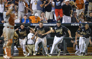 Photo - Vanderbilt players dash from the dugout as a single by Tyler Campbell in the 10th inning scored Rhett Wiseman for a 4-3 win over Texas in an NCAA baseball College World Series game in Omaha, Neb., Saturday, June 21, 2014. Vanderbilt advances to the championship series. (AP Photo/Ted Kirk)