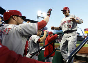Photo - Cincinnati Reds' Joey Votto, right, is congratulated by teammate Zack Cozart, left, after scoring on a two-run triple by Jay Bruce during the first inning of a baseball game against the St. Louis Cardinals on Tuesday, April 8, 2014, in St. Louis. (AP Photo/Jeff Roberson)