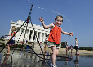 Photo -   Sophie, 3, from Connecticut, frolics with a water sprinkler set up at the National Mall near the Lincoln Memorial, rear, in Washington Saturday, July 7, 2012. The heat gripping much of the country is set to peak Saturday in many places, including some Northeast cities, where temperatures close to or surpassing 100 degrees are expected. (AP Photo/Manuel Balce Ceneta)