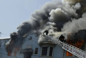 Photo -   San Francisco firefighters battle a four-alarm fire at a residential and commercial building on the corner of Valencia Street and Duboce Avenue in San Francisco, Sunday, May 6, 2012. (AP Photo/Jeff Chiu)