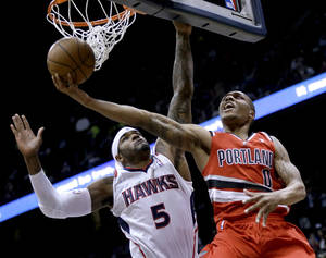 Photo - Portland Trail Blazers' Damian Lillard, right, puts up a shot against Atlanta Hawks' Josh Smith during the third quarter of an NBA basketball game, Friday, March 22, 2013, in Atlanta. Portland won 104-93. (AP Photo/David Goldman) ORG XMIT: GADG111