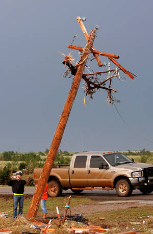photo - A man stands beneath a  bent utility pole to take photos of a home  on SH 74 near Cashion. destroyed by a tornado Tuesday afternoon, May 24, 2011. Branches of a tree are snagged in the wires at the top of the pole.  Photo by Jim Beckel, The Oklahoman