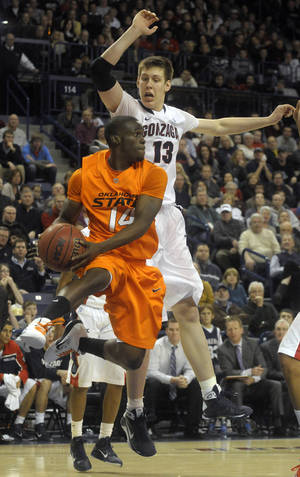 Photo - Oklahoma State's Ray Penn (14) makes a pass in front of Gonzaga's Kelly Olynyk (13) on Friday night. AP photo