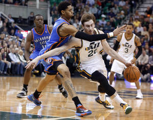 Photo - Utah Jazz guard Gordon Hayward (20) is defended by Oklahoma City Thunder guard Jeremy Lamb (11) during the second half of their NBA basketball game in Salt Lake City, Tuesday, Jan. 7, 2014. The Jazz won 112-101. (AP Photo/Jim Urquhart)