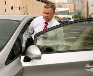 Photo - FILE - Former Fiesta Bowl executive director John Junker gets into his car outside the Sandra Day O'Connor U.S. courthouse after being sentenced in Phoenix on in this March 13,  2014 file photo. The sentencing Thursday March 20, 2014 of 58-year-old John Junker in Maricopa County Superior Court will mark the end of criminal cases that arose from the contribution scandal that jeopardized the bowl's NCAA license and led to the ouster of the longtime bowl leader. (AP Photo/The Arizona Republic, Michael Schennum, File)  MARICOPA COUNTY OUT; MAGS OUT; NO SALES