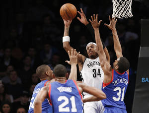 Photo - Brooklyn Nets forward Paul Pierce (34) passes with Philadelphia 76ers power forward Lavoy Allen (50) and Philadelphia 76ers guard Hollis Thompson (31) defending in the second half of their NBA basketball game at the Barclays Center, Monday, Feb. 3, 2014 in New York. The Nets defeated the Sixers 108-102. (AP Photo/Kathy Willens)