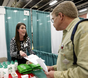 Photo - In this April 22, 2014 photo, Erin Wilson, of Hannaford Bros. supermarket company, left, talks with a job seeker during a job fair Columbia-Greene Community College in Hudson, N.Y. The Labor Department releases weekly jobless claims on Thursday, April 24, 2014. (AP Photo/Mike Groll)