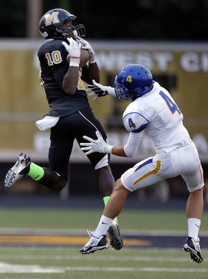 Photo - Midwest City's Will Sunderland makes a catch in front of Stillwater's TJ Black during the high school football game between Midwest City and Stillwater at Midwest City, Okla., Friday, Sept. 13, 2013. Photo by Sarah Phipps, The Oklahoman