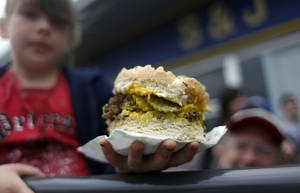 photo - Alaina Weaver holds her portion of the World's Largest Fried Onion Hamburger during the El Reno Fried Onion Burger Day Festival in 2010. The 24th edition of the festival is Saturday.