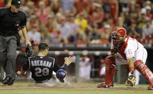 Photo - Colorado Rockies' Nolan Arenado (28) scores on a double hit by Justin Morneau in the ninth inning of a baseball game against the Cincinnati Reds, Friday, May 9, 2014, in Cincinnati. Reds' Brayan Pena, right, catches as umpire Cory Blaser makes the call. Cincinnati won 4-3. (AP Photo/Al Behrman)