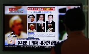 Photo - A man watches the TV news program on the reward poster of Yoo Byung-eun at the Seoul Train Station in Seoul, South Korea, Friday, May 23, 2014. South Korea is offering a big bounty to find the mysterious billionaire thought to be the owner a ferry that sank last month, leaving more than 300 people dead or missing. (AP Photo/Lee Jin-man)