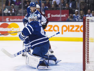 Photo - Toronto Maple Leafs goalie Jonathan Bernier looks back as the puck rings off the crossbar on a Colorado Avalanche shot during the first period of an NHL hockey game in Toronto on Tuesday, Oct. 8, 2013. (AP Photo/The Canadian Press, Nathan Denette)