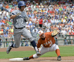 Photo - UC Irvine's Taylor Sparks (25) reaches first base on a throwing error by second baseman Brooks Marlow, unseen, as Texas first baseman Kacy Clemens (42) can't catch the ball, in the first inning of an NCAA baseball College World Series game in Omaha, Neb., Saturday, June 14, 2014. (AP Photo/Ted Kirk)