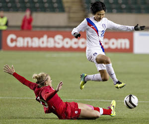 Photo - South Korea' s Minji Yeo (22) jumps over Canada's Lauren Sesselmann (10) during the second half of an international friendly soccer match, Wednesday, Oct. 30, 2013, in Edmonton, Alberta. (AP Photo/The Canadian Press, Jason Franson)