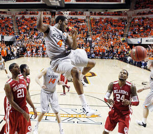 Photo - OSU's Brian Williams (4) dunks the ball in the first half as OU's Cameron Clark (21) and Romero Osby (24) look on during the Bedlam men's college basketball game between the Oklahoma State University Cowboys and the University of Oklahoma Sooners at Gallagher-Iba Arena in Stillwater, Okla., Monday, Jan. 9, 2012. Photo by Nate Billings, The Oklahoman