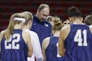 Photo - BYU coach Jeff Judkins and players take time to pray prior to NCAA college basketball practice in Lincoln, Neb., Friday, March 28, 2014. BYU will play Connecticut in a Lincoln Regional women's semifinal basketball game on Saturday. (AP Photo/Nati Harnik)