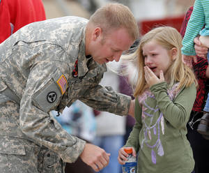 photo - Sierria, 6, cries as she says goodbye to her dad Warrant Officer John Jenkins following an Oklahoma Aviation Command mobilization ceremony  for Detachment 1, Company C, 2-149th General Support Aviation Battalion at the Army Aviation Support Facility in Lexington, Okla., Sunday, Sept. 16, 2012. The soldiers will receive additional training at Fort Hood before being deployed to Afghanistan. Photo by Sarah Phipps, The Oklahoman