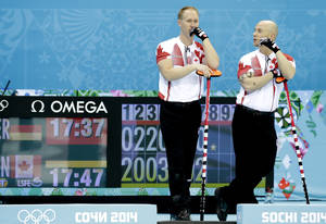 Photo - Canada's skip, Brad Jacobs, left, and Ryan Fry, right, discuss tactics during the men's curling competition against Germany at the 2014 Winter Olympics, Monday, Feb. 10, 2014, in Sochi, Russia. (AP Photo/Wong Maye-E)