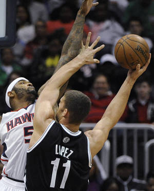 Photo - Brooklyn Nets center Brook Lopez (11) shoots over Atlanta Hawks forward Josh Smith during the first half of an NBA basketball game in Atlanta, Saturday, March 9, 2013. (AP Photo/David Tulis)