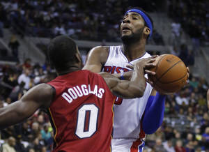 Photo - Miami Heat guard Toney Douglas (0) knocks the ball out of the hands of Detroit Pistons center Andre Drummond, right, during the first half of an NBA basketball game on Friday, March 28, 2014, in Auburn Hills, Mich. (AP Photo/Duane Burleson)