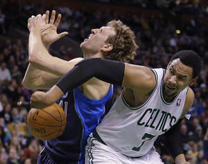 Photo - Boston Celtics center Jared Sullinger (7) knocks the ball away as he fouls Dallas Mavericks power forward Dirk Nowitzki (41) going to the hoop during the second half of their NBA basketball game in Boston, Sunday, Feb. 9, 2014. The Mavericks defeated the Celtics 102-91. (AP Photo/Stephan Savoia)