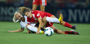 Photo - Portland's Kathryn Williamson,left, and  Western New York defender Angela Salem, right, battle for the ball during the inaugural NWSL championship Saturday Aug. 31, 2013 in Rochester, NY as they played for the title.  (AP Photo/The Oregonian, Jamie Francis)
