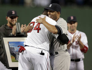 Photo - New York Yankees relief pitcher Mariano Rivera, right, hugs Boston Red Sox's David Ortiz during a tribute for Rivera before the start of a baseball game at Fenway Park, in Boston, Sunday, Sept. 15, 2013. (AP Photo/Steven Senne)