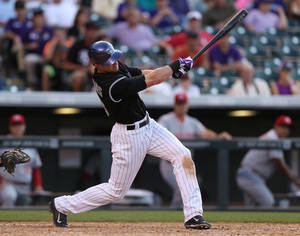 Photo - Colorado Rockies' Drew Stubbs follows through with his swing after connecting for a three-run walkoff home run against the Cincinnati Reds in the ninth inning of the Rockies' 10-9 victory in a baseball game in Denver, Sunday, Aug. 17, 2014. (AP Photo/David Zalubowski)