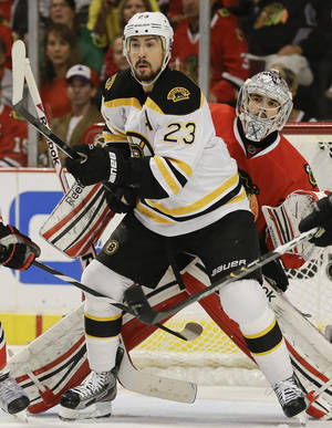 Photo - Boston Bruins center Chris Kelly (23) looks for a pass as Chicago Blackhawks goalie Corey Crawford (50) looks on in the first period during Game 2 of the NHL hockey Stanley Cup Finals, Saturday, June 15, 2013, in Chicago. (AP Photo/Nam Y. Huh)